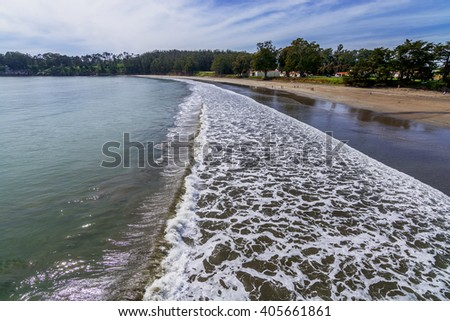 Beautiful shimmering blue sea, white clouds & waves, gently crashing on San Simeon Beach, while people are enjoying a walk on the beach & beautiful green trees in the background, near San Simeon, CA. - stock photo