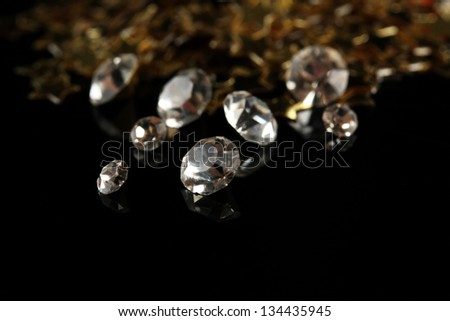 Beautiful shining crystals (diamonds) and golden stars, on black background - stock photo
