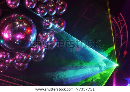 Beautiful shiny balls and colorful rays on ceiling in night club - stock photo