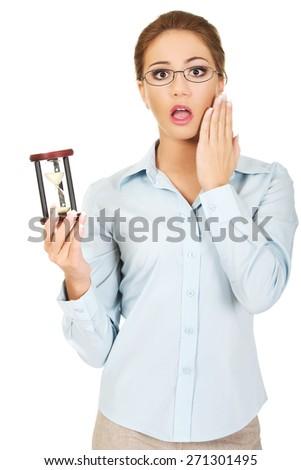Beautiful shocked businesswoman holding a sandglass. - stock photo