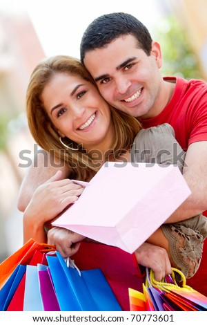 Beautiful shopping couple smiling and looking happy - stock photo