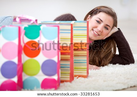 Beautiful shopping girl lying on the floor with some bags - stock photo