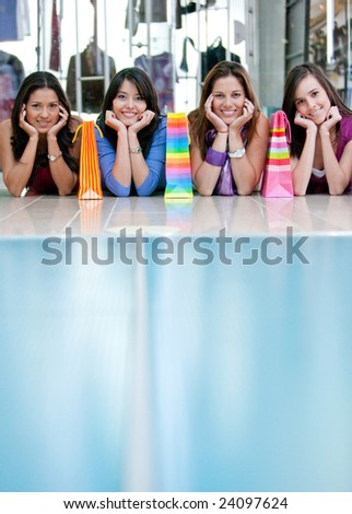 Beautiful shopping girls lying on the floor in a mall with some bags - stock photo