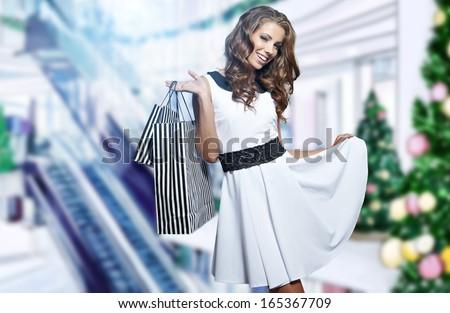 Beautiful shopping woman at a draw christmas store - stock photo
