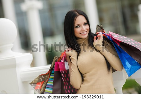 Beautiful shopping woman happy holding shopping bags outdoor. Walking in the street