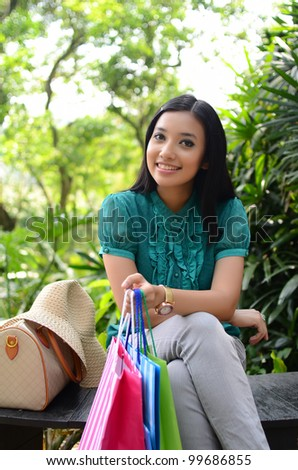 Beautiful shopping woman happy holding shopping bags take rest at garden and smile - stock photo