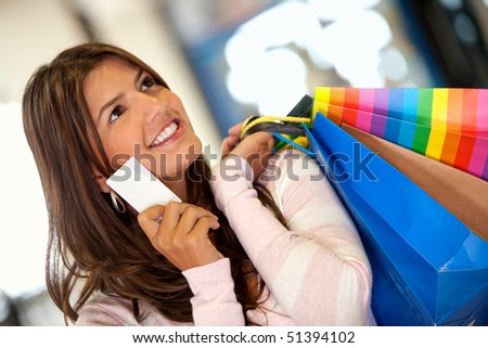 Beautiful shopping woman holding a credit card - stock photo