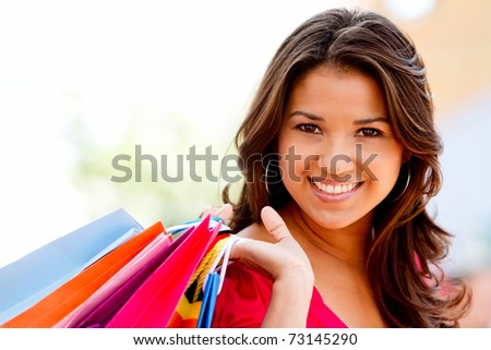 Beautiful shopping woman holding bags at a mall - stock photo