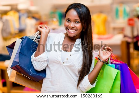 Beautiful shopping woman smiling and holding bags - stock photo