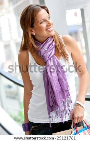 Beautiful shopping woman smiling at a mall - stock photo