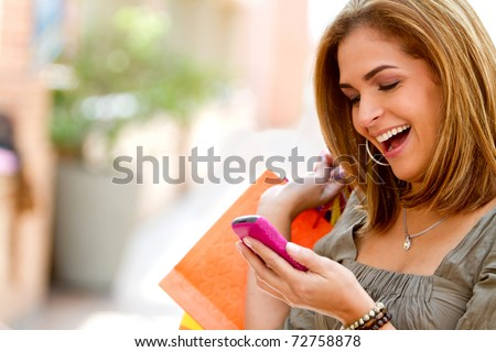 Beautiful shopping woman texting on her cell phone - stock photo