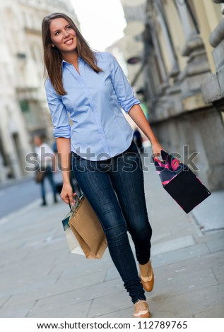 Beautiful shopping woman walking with bags looking happy - stock photo