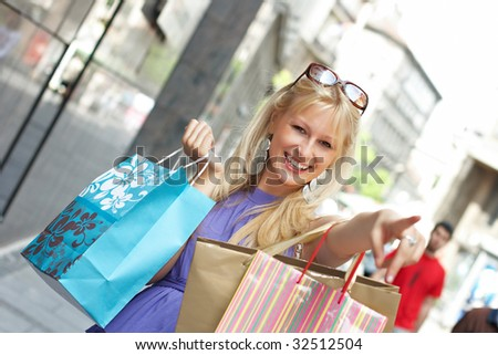 Beautiful shopping woman with bags point away.