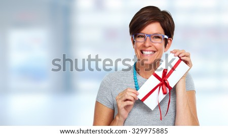 Beautiful shopping woman with envelope gift over blue background.