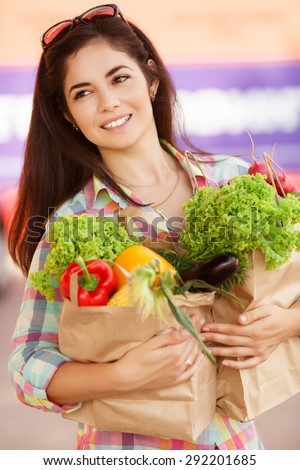 Beautiful shopping woman with vegetables, happy young girl in grocery shop with purchase bags full of organic vegetables, smiling female at supermarket buying food, instagam style filters, series