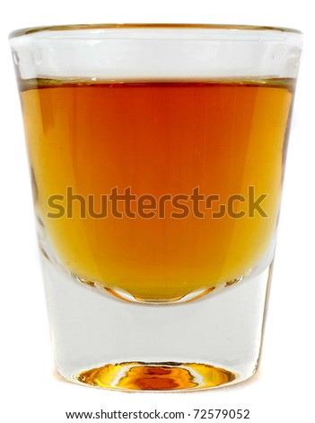 Beautiful side on shot of a shot glass full of brown whiskey or brandy - stock photo
