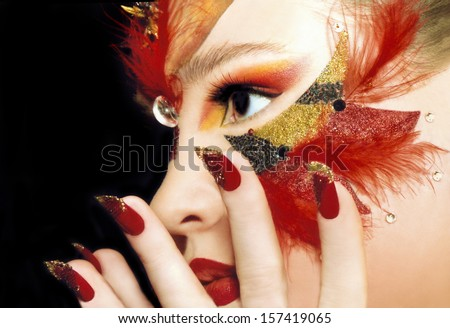 Beautiful sight of the girl in the red make-up,red lips and nails,sequins and feathers. - stock photo