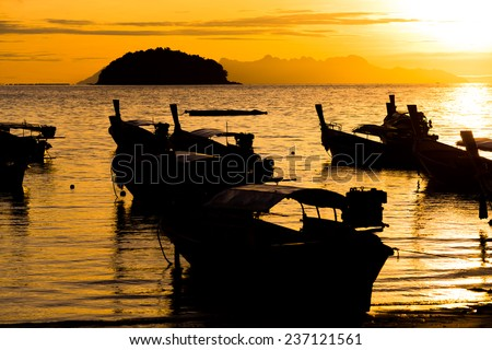 Beautiful silhouette fisherman boat with sunrise. - stock photo