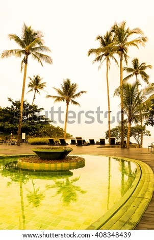 Beautiful Silhouette luxury umbrella and chair around swimming pool in hotel pool resort with coconut palm tree at sunrise times - Vintage Filter and Boost up color Processing