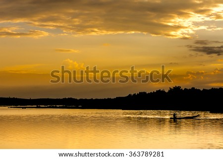 Beautiful Silhouette Mountain Lake and Fisherman's boat at Twilight sunset time - stock photo