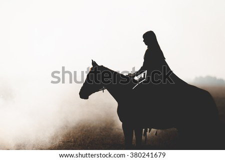 Beautiful silhouette of a girl who rides a horse through the thick smoke on a white background. The woman and the horse stand and look into the distance in the fog, backlit