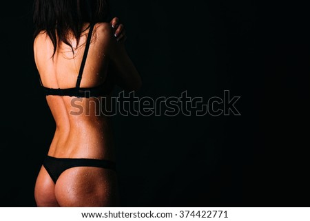 Beautiful silhouette of attractive tanned girl with water drops on a body - stock photo