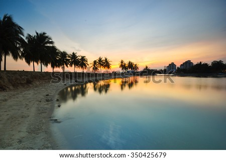 Beautiful silhouette of coconut trees at seaside. Nature composition. - stock photo