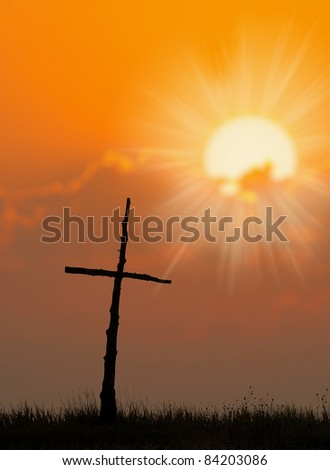 Beautiful silhouette of Cross and sunrise over a meadow on a cool fall morning. - stock photo