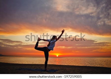 Beautiful silhouette of woman performing yoga on the sea, paradise dawn