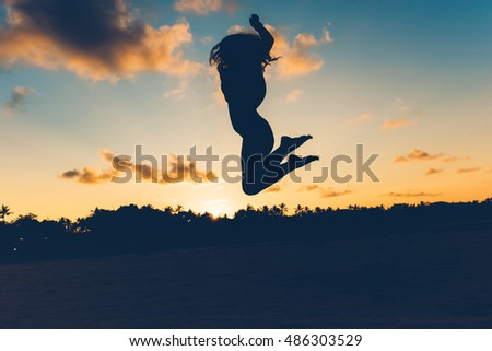 Beautiful silhouette portrait of summer girl jumping on white sand in exotic island at sunset. Serenity, relaxation, mindfulness, stress and carefree concepts.