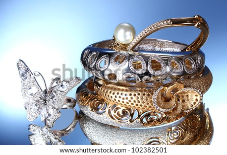 Beautiful silver and gold bracelets and ring on blue background - stock photo