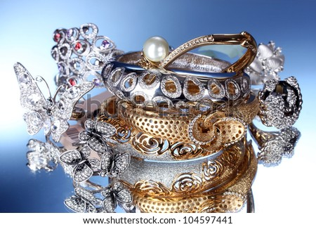 Beautiful silver and gold bracelets and rings on blue background - stock photo
