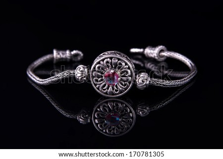 Beautiful silver bracelet on black background - stock photo