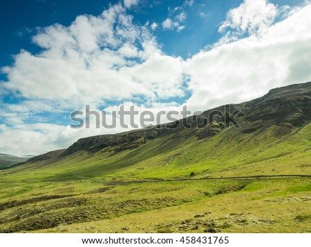 Beautiful simple landscape with green field and mountains.