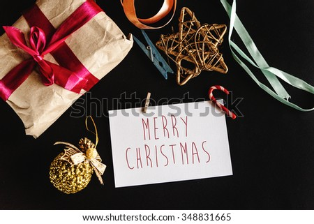 beautiful simple present in craft paper with ribbons, greeting card and toys, merry christmas text