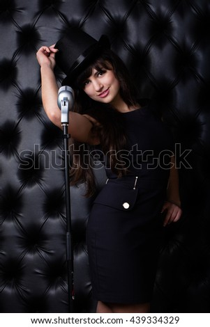 Beautiful singer singing with a retro microphone. Brunette chanteuse in black hat on black background.  - stock photo