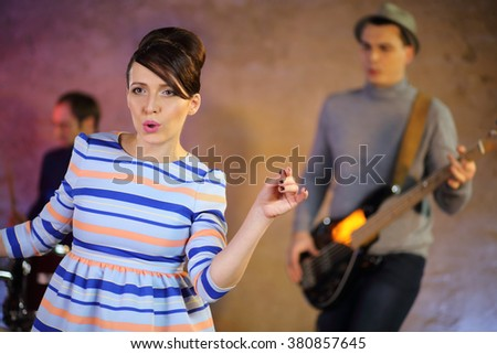 Beautiful singer with dark hair in a striped dress sings in front of musicians - stock photo