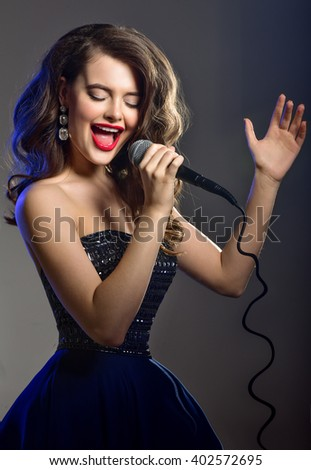 Beautiful Singing Girl. Beauty Woman with Microphone  Glamour Model Singer. Karaoke song - stock photo