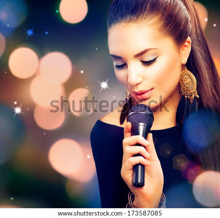 Beautiful Singing Girl. Beauty Woman with Microphone over Blinking bokeh night background. Glamour Model Singer. Karaoke song - stock photo