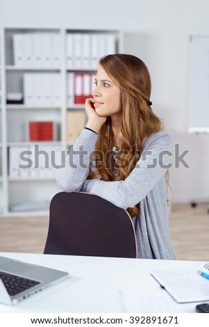 Beautiful single female young worker staring off to the side as if daydreaming while leaning on chair beside desk with laptop