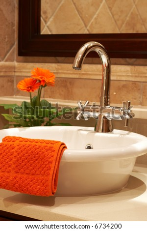 Beautiful sink in a bathroom with towel on it and a flower - stock photo