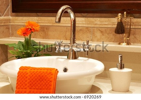 Beautiful sink in a bathroom with towel on it and a flower. Focus is on the tap