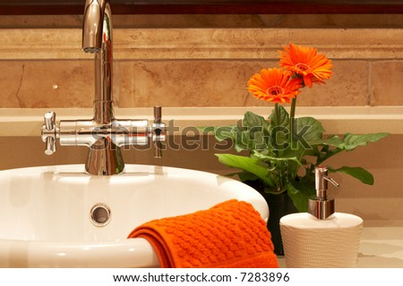 Beautiful sink in a bathroom with towel on it and a flower. Focus is on the tap - stock photo