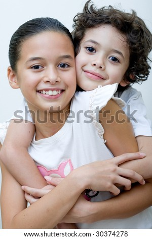 Beautiful sister and brother sharing a loving hug - stock photo
