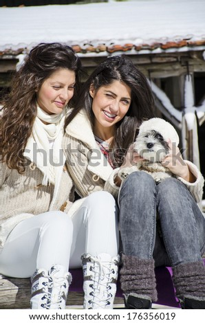 beautiful sisters enjoying the time spent with their little dog in the winter mountain