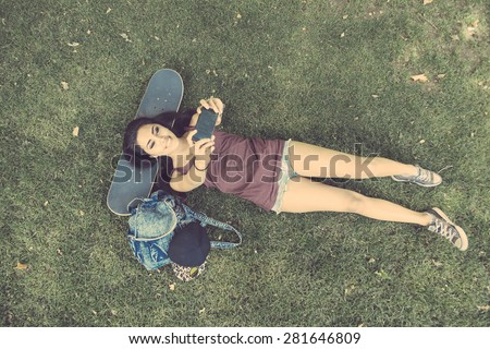 Beautiful skater girl taking a selfie at park, top view. She is lying on the grass with the head on the skate. She is half caucasian and half filipina, she wears short jeans and a purple tank top. - stock photo
