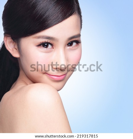 Beautiful Skin care woman Face smile to you isolated on blue background. asian Beauty - stock photo