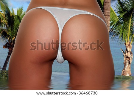 Beautiful skinny well tanned bottom with a white panty string in front of the ocean sea. Perfect female form and standing in the pool