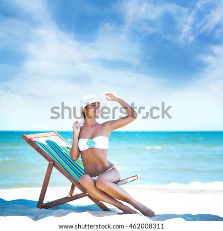 Beautiful, skinny, young woman wearing a hat in alluring bikini sitting on a deckchair on the beach.