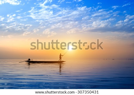 Beautiful sky and Silhouettes of Minimal fisherman at the lake, Thailand. - stock photo